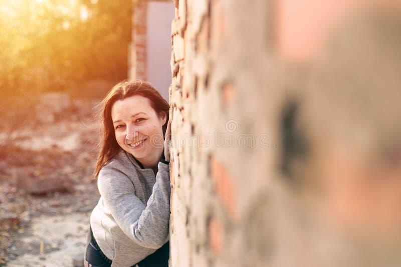 Jeune femme naturelle jouant au caché au vieux mur photographie stock
