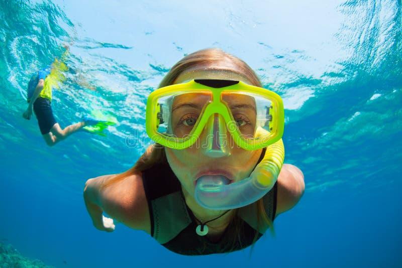 Jeune femme naviguant au schnorchel avec des poissons de récif coralien photographie stock
