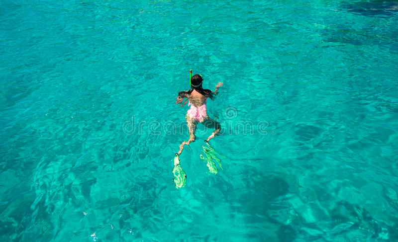 Jeune femme naviguant au schnorchel dans l'eau tropicale dessus image libre de droits