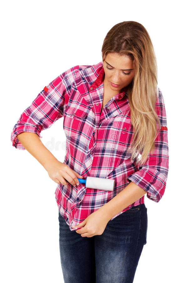 Jeune femme nettoyant sa chemise avec le rouleau de fibre images stock