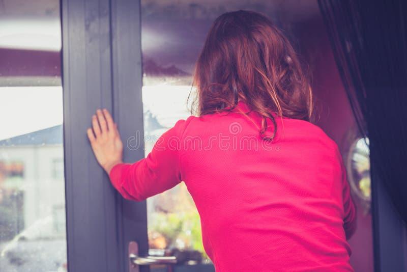 Jeune femme nettoyant ses fenêtres photos stock