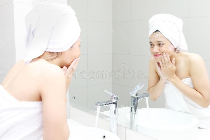 Jeune femme nettoyant son visage dans la salle de bains photo libre de droits