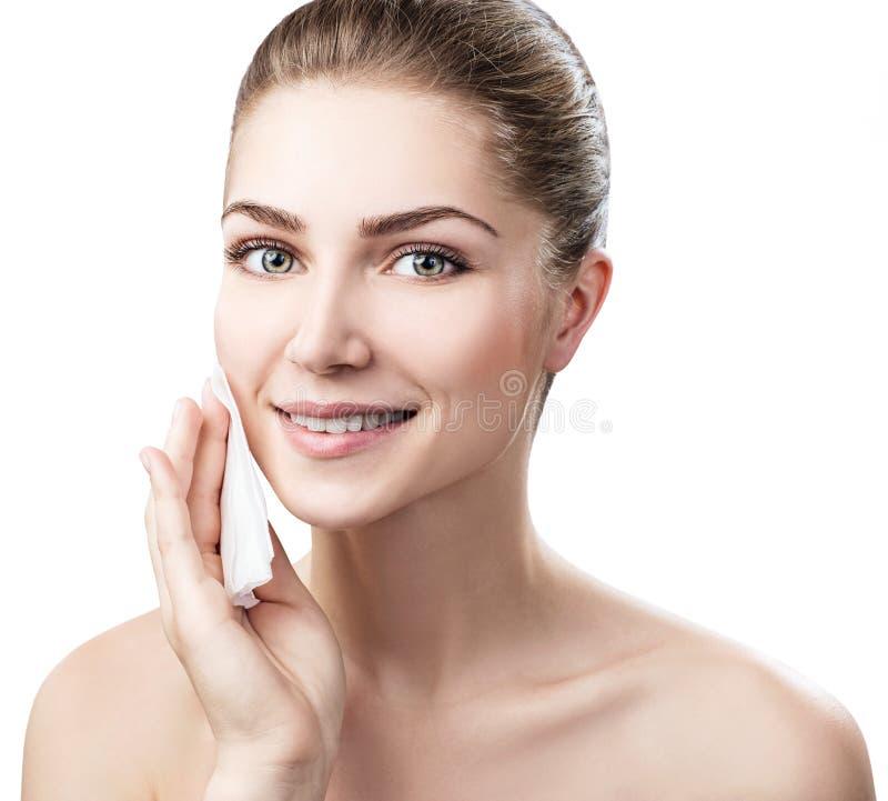 Jeune femme nettoyant son visage par des serviettes image stock