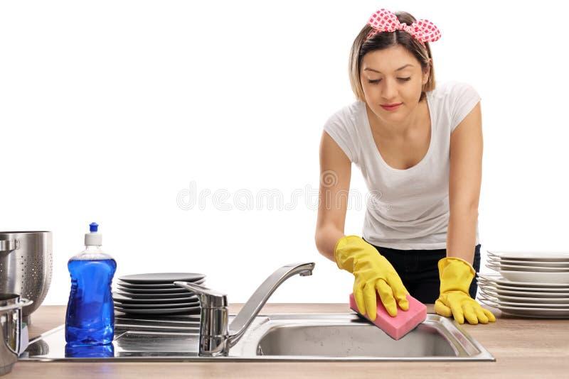 Jeune femme nettoyant un évier avec une éponge images libres de droits