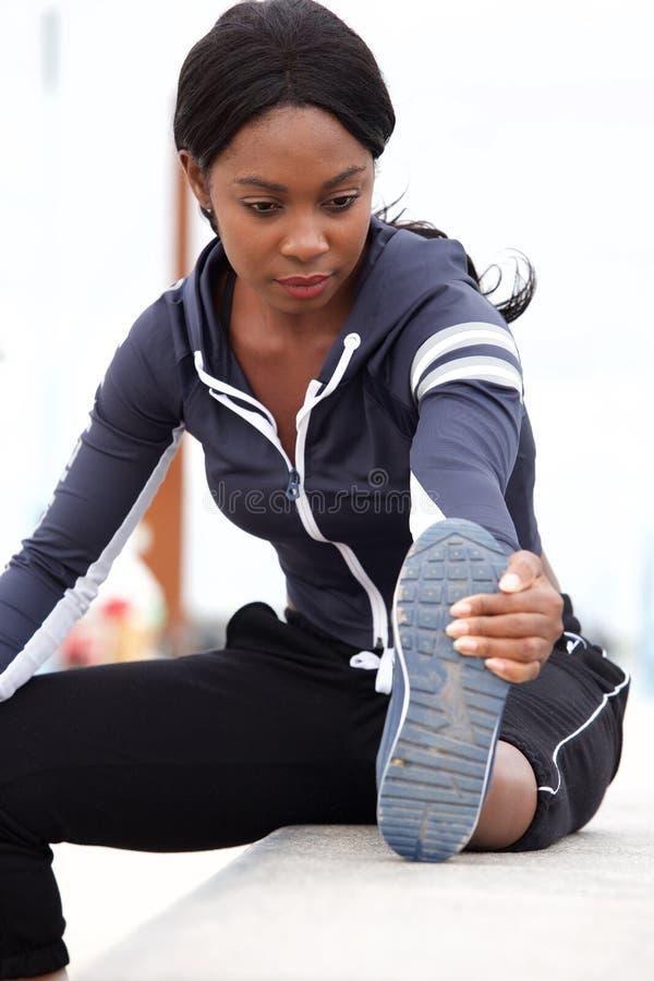 Jeune femme noire de sports étirant des muscles dehors images libres de droits