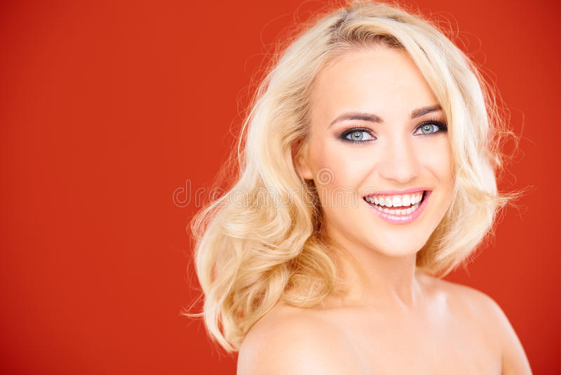 Jeune femme nue blonde gaie regardant l'appareil-photo image stock
