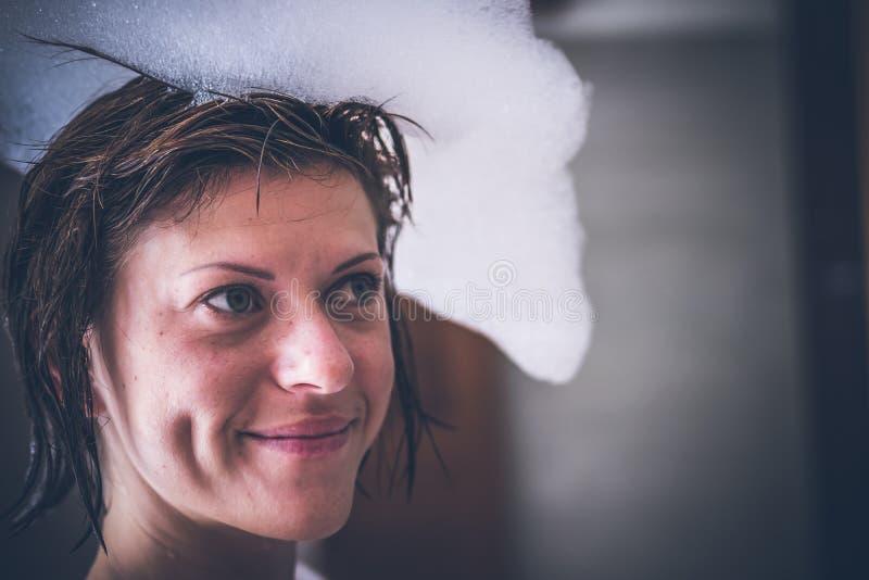Jeune femme nue sexy décontractée dans le bain avec la mousse sur sa tête, villa de luxe, île tropicale de Bali, Indonésie photos libres de droits