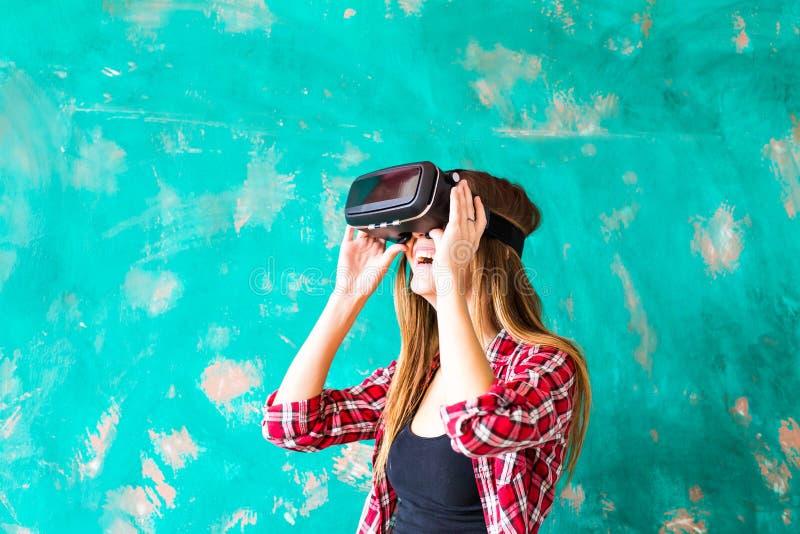 Jeune femme observant cependant le dispositif de VR photographie stock