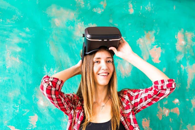 Jeune femme observant cependant le dispositif de VR image libre de droits