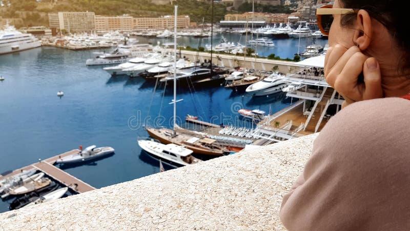 Jeune femme observant des yachts dans le port, rêvant de l'oligarque et de la vie riche image libre de droits
