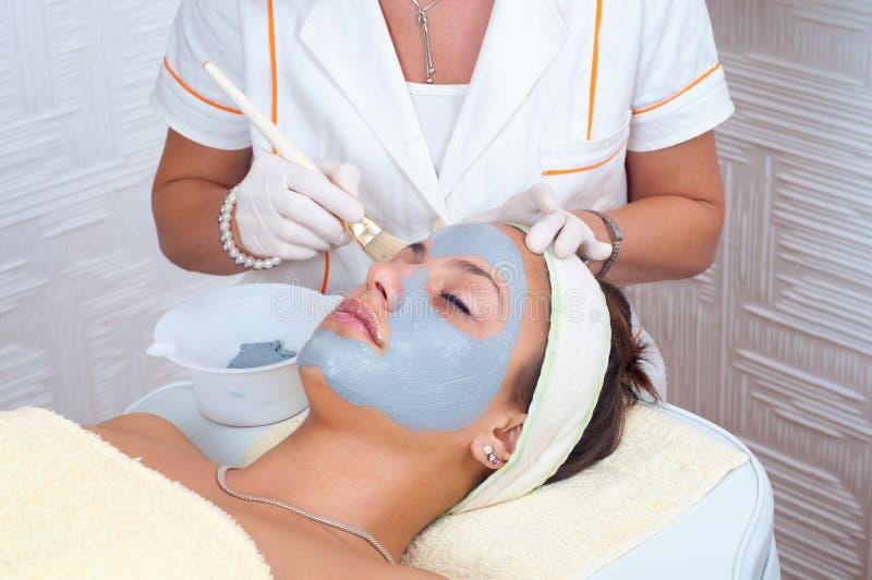 Jeune femme obtenant le masque facial naturel sur son visage images stock