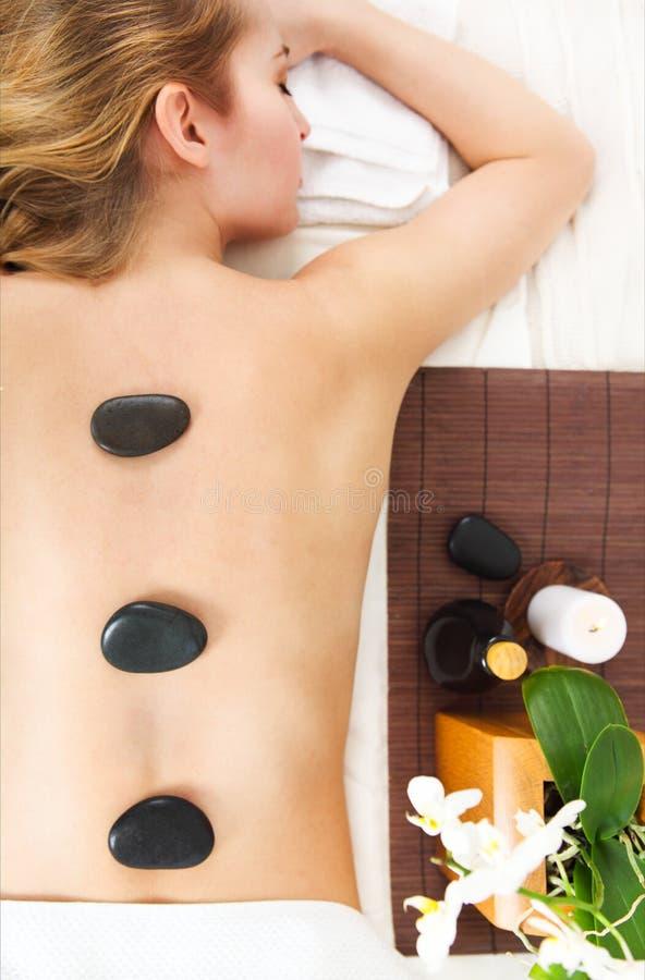 Jeune femme obtenant le massage en pierre chaud dans le salon de station thermale photo libre de droits