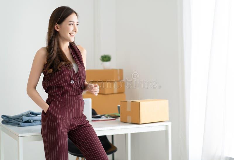Jeune femme occasionnelle asiatique travaillant la petite position d'entrepreneur recherchant et souriant ? la maison bureau Cr?e photos stock