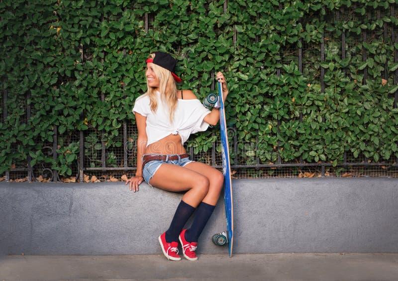 Jeune femme occasionnelle attirante avec une planche à roulettes image libre de droits