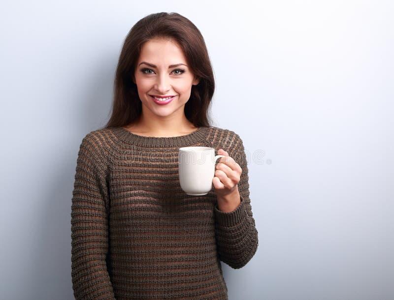 Jeune femme occasionnelle de sourire avec la tasse de thé semblant heureuse photo stock