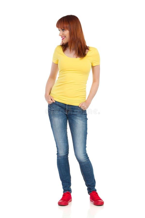 Jeune femme occasionnelle de sourire se tenant avec des mains dans des poches et regardant loin photographie stock libre de droits