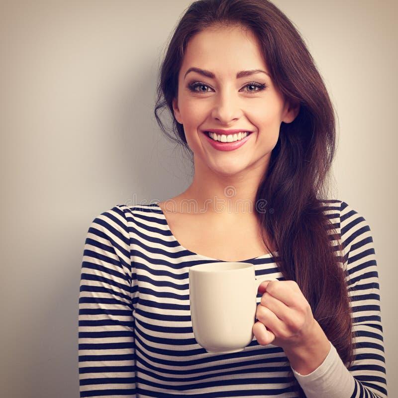 Jeune femme occasionnelle de sourire toothy heureuse avec la tasse de thé cru photo libre de droits