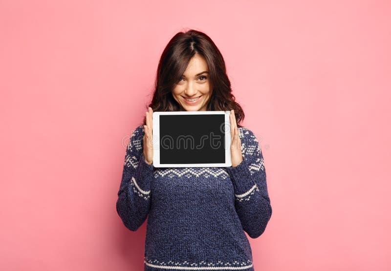 Jeune femme occasionnelle montrant un écran propre de comprimé photo stock