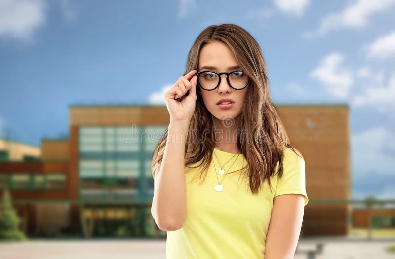 Jeune femme ou adolescente en verres au-dessus d'école photographie stock