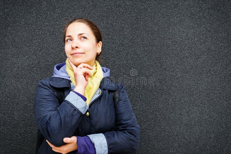 Jeune femme ou fille rêveuse mignonne, souriant et regardant le fond texturisé noir de mur photos libres de droits