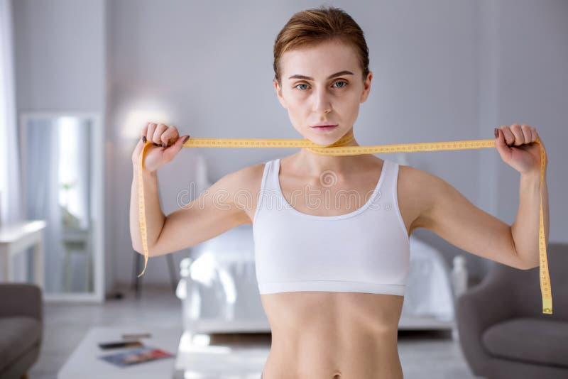 Jeune femme pâle tenant une bande de centimètre photographie stock