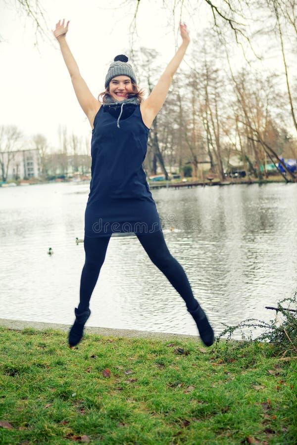 Jeune femme par l'eau sautant dans le ciel photos stock