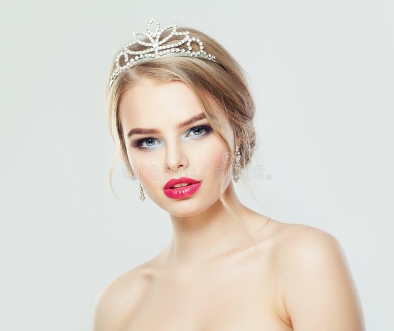 Jeune femme parfaite avec les cheveux blonds, le maquillage et le portrait de couronne de diadème de diamants photographie stock