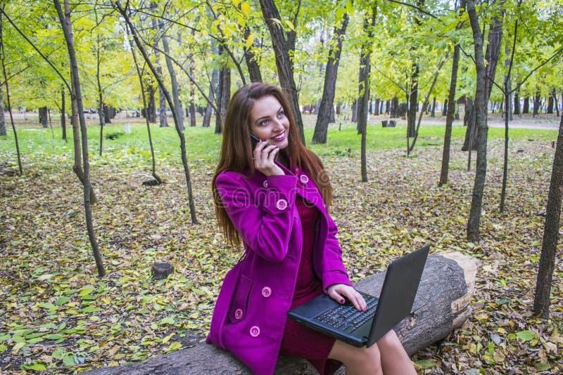 Jeune femme parlant au téléphone Est tout près un ordinateur portable photographie stock libre de droits