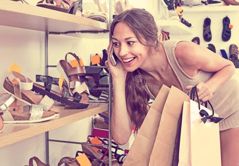 Jeune femme parlant au téléphone portable dans la boutique images libres de droits