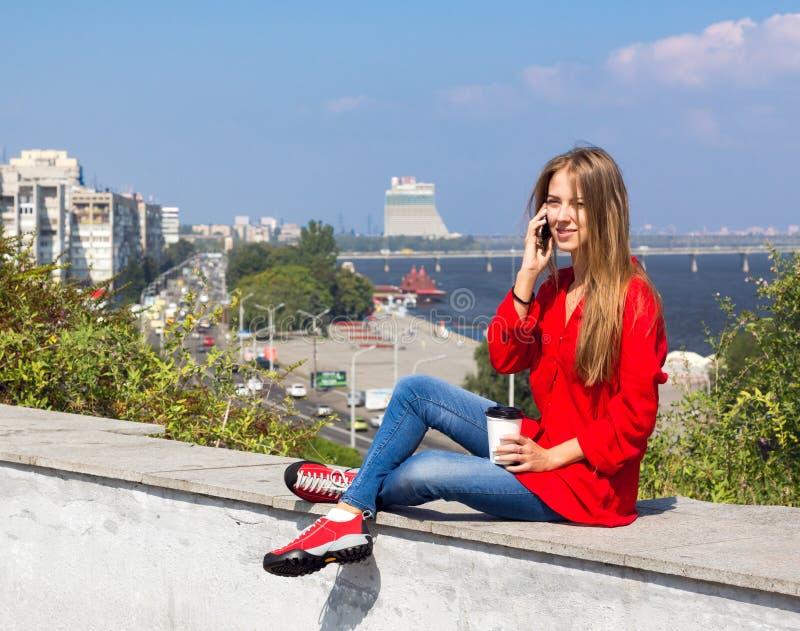 Jeune femme parlant au téléphone se reposant sur le parapet dans la ville images libres de droits