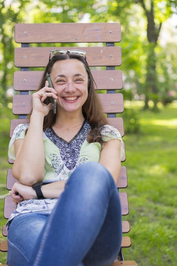 Jeune femme parlant sur le smartphone et riant dans le parc sur le banc Belle femme se reposant sur un banc de parc et utilisant  images stock