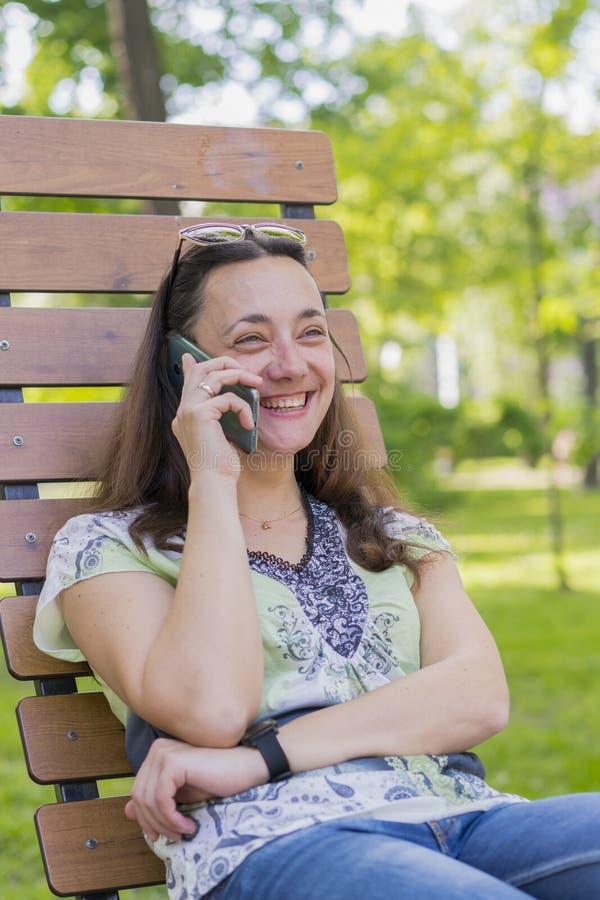 Jeune femme parlant sur le smartphone et riant en parc sur la belle d?tente femelle de banc sur un banc de parc et employer photos libres de droits