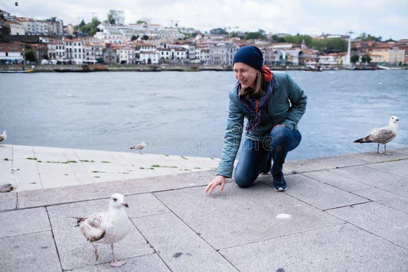 Jeune femme parmi des mouettes sur le remblai à Ribeira de rivière de Douro, Porto photo stock
