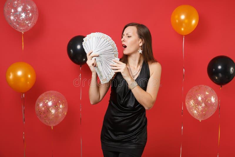 Jeune femme passionnée dans la robe noire célébrant, tenant un bon nombre de paquet de dollars, comptant l'argent d'argent liquid images stock