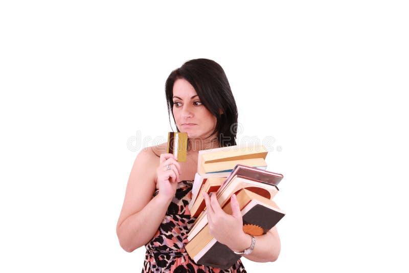 Jeune femme payant les factures élevées avec par la carte de crédit images stock
