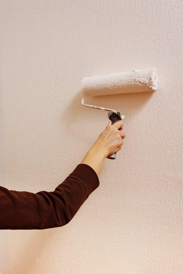 Jeune femme peignant son mur à la maison images libres de droits
