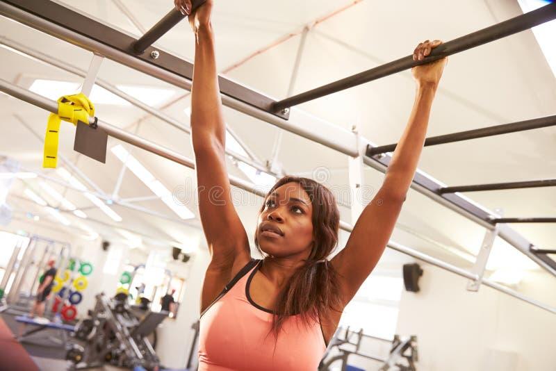 Jeune femme pendant des barres de singe à un gymnase photos stock