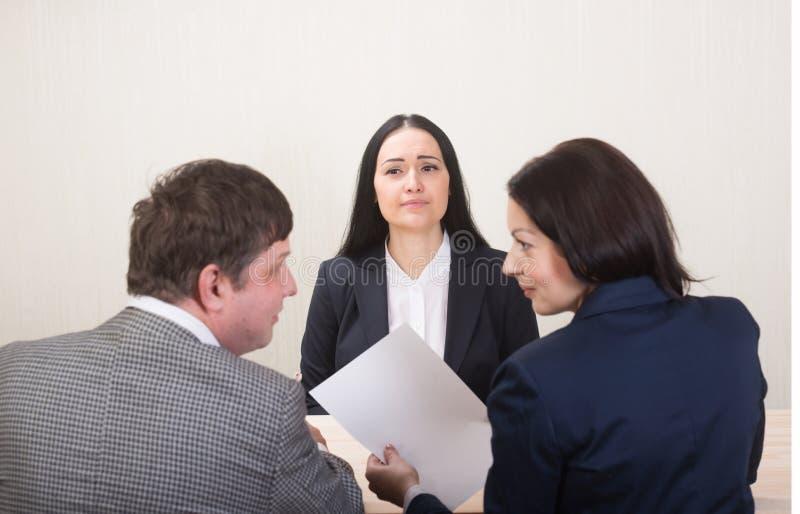 Jeune femme pendant l'entrevue d'emploi et membres des managemen image libre de droits