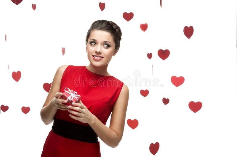 Jeune femme pensif retenant le cadeau rouge photographie stock