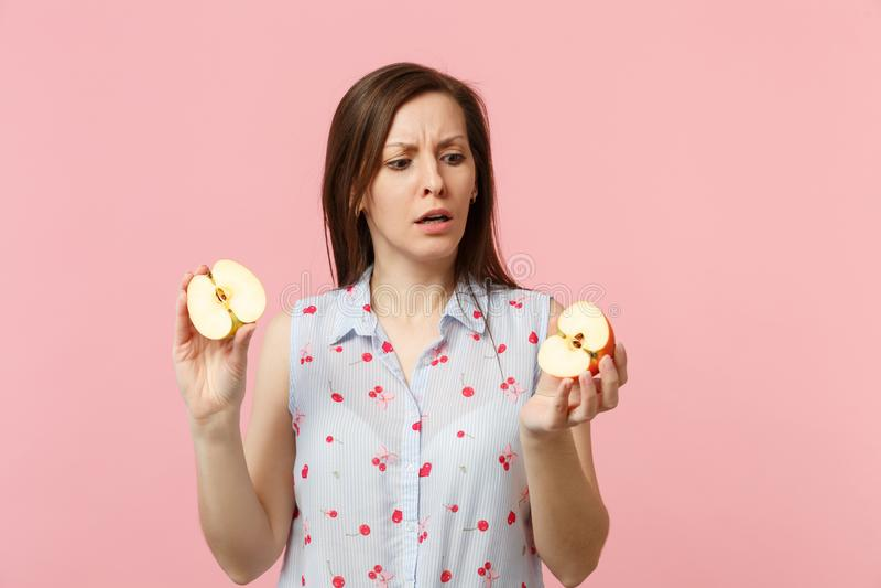 Jeune femme perplexe dans des vêtements d'été se tenant dans des halfs de mains du fruit mûr frais de pomme d'isolement sur le pa photos stock