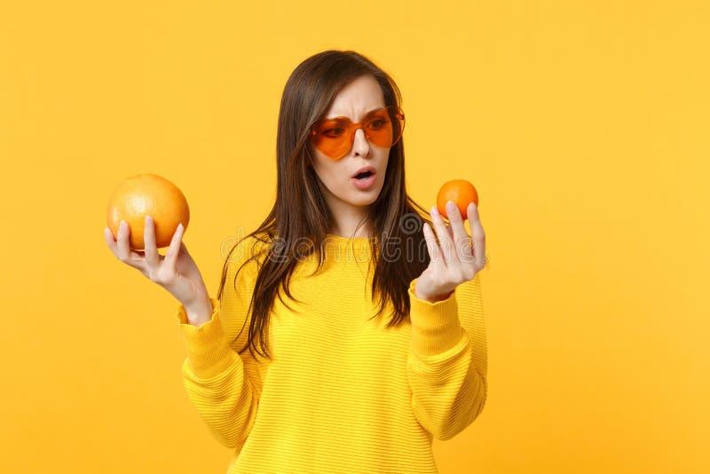 Jeune femme perplexe en verres de coeur se tenant en mandarine mûre fraîche de mains, fruit orange d'isolement sur le fond jaune  photographie stock