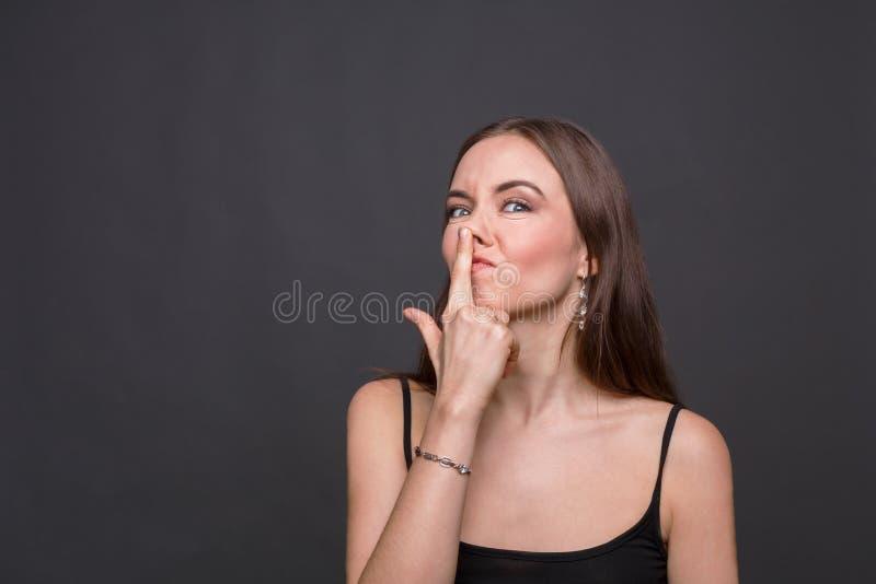 Jeune femme plaisantant et touchant son nez images libres de droits
