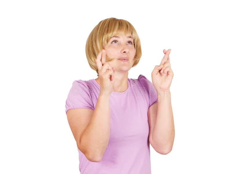 Jeune femme pleine d'espoir de portrait de plan rapproché croisant ses doigts photographie stock libre de droits
