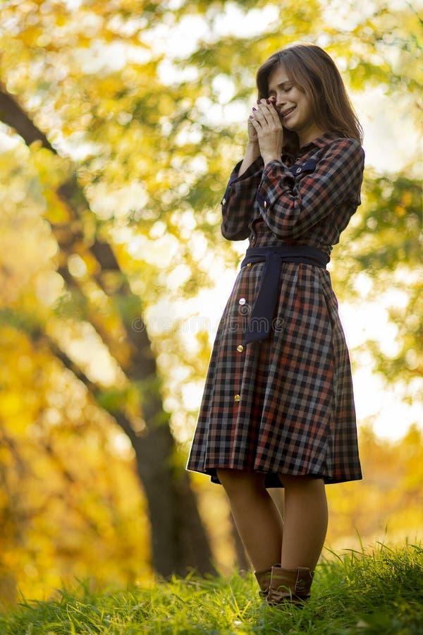 jeune femme pleurant tout en priant à Dieu dans la nature d'automne, le concept de la spiritualité et la religion photographie stock