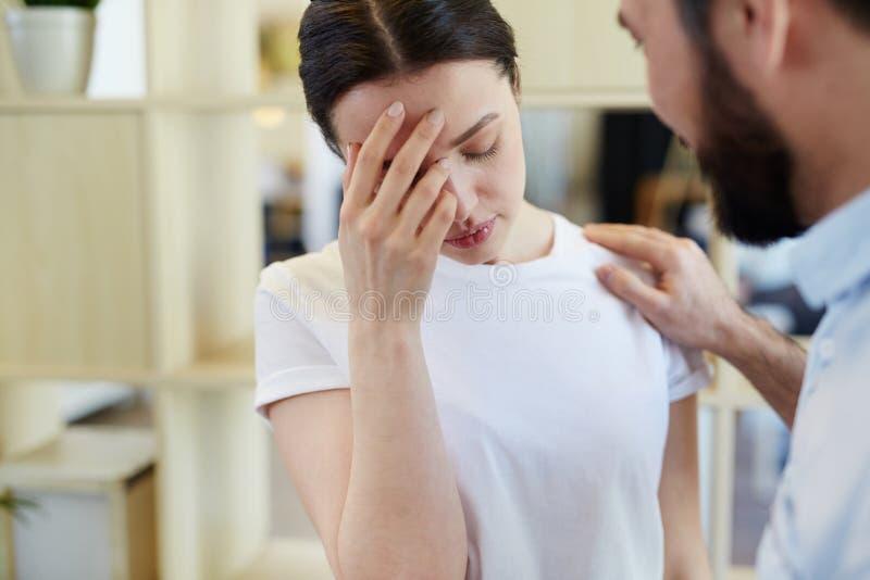 Jeune femme pleurante de consolation d'homme photographie stock libre de droits