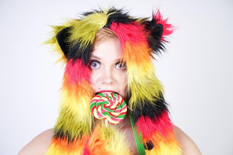 Jeune femme plus de charme de taille dans le chapeau de fourrure fait de fibres multicolores avec des oreilles et des pattes de c photographie stock