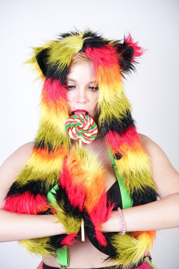 Jeune femme plus de charme de taille dans le chapeau de fourrure fait de fibres multicolores avec des oreilles et des pattes de c image libre de droits
