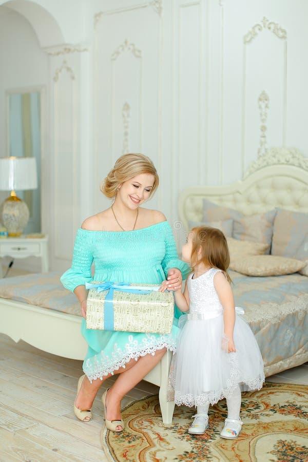 Jeune femme portant la robe bleue se reposant avec la petite fille et gardant le présent photographie stock