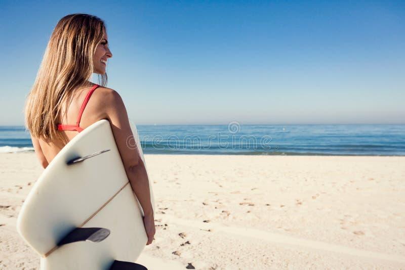 Jeune femme portant une planche de surf à la plage photo stock