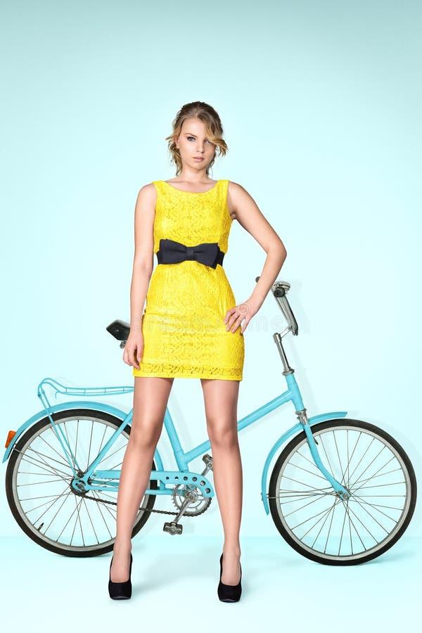 Jeune femme posant avec la bicyclette image stock